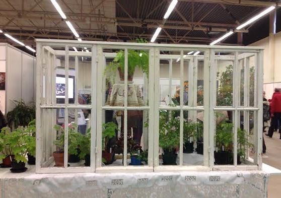 Vanhoista ikkunoista tehty pikkuinen kasvihuone