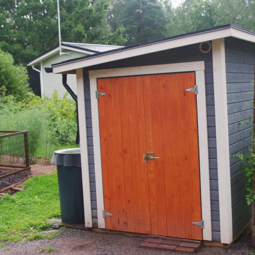 Pieni siniharmaa puutarhavaja, jossa oranssi ovi