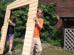 Kaksi miestä kantaa puutarhavajan seinäelementtiä