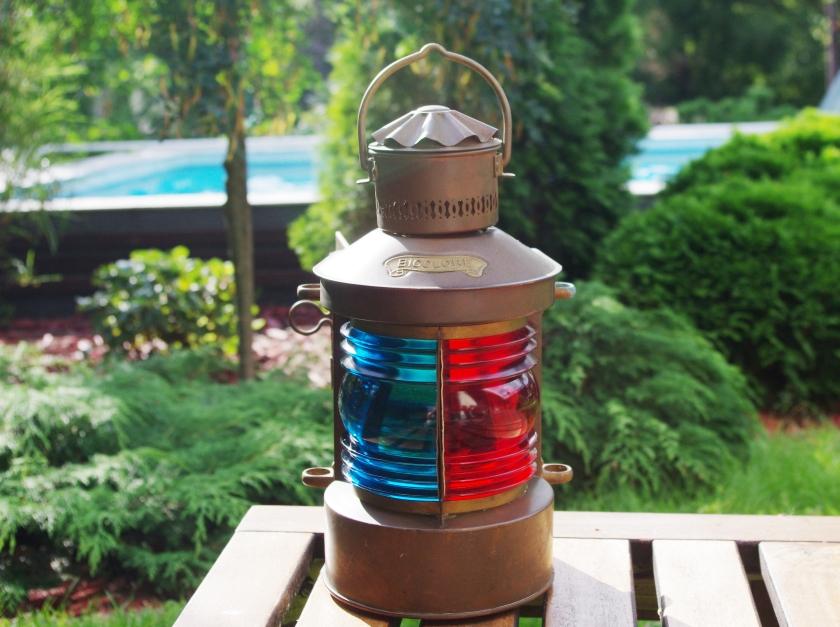 Laivalyhty, jonka vasen puoli on vihreää/sinistä lasia ja oikea puoli punaista lasia