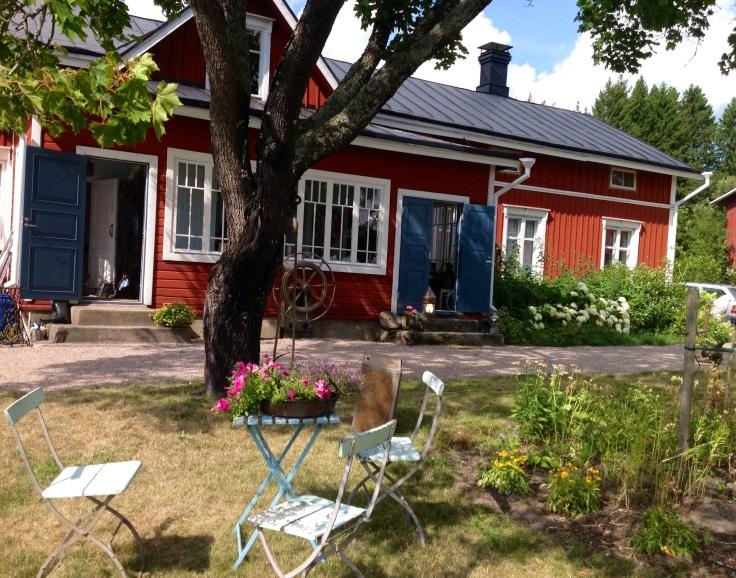 Punainen puutalo ja pihapiiriä, jossa pöytä ja tuolit