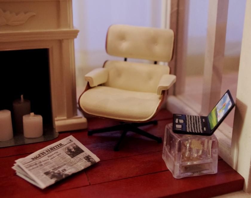 Eamesin nojatuolin pienoismalli ja sivupöytä, jolla läppäri.