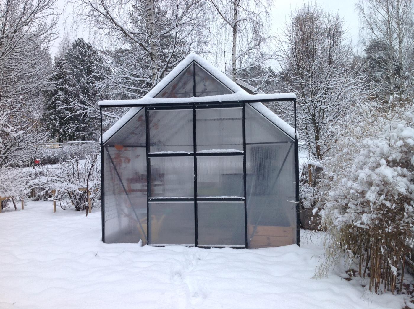 Talvinen kasvihuone lumisella pihalla