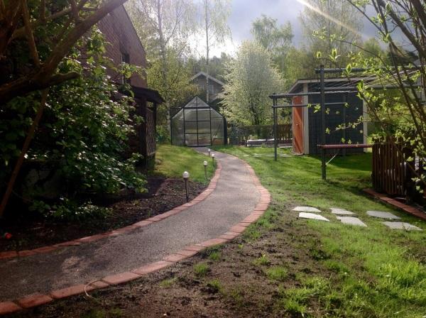 Betonikivillä reunustettu kivituhkapolku puutarhassa.