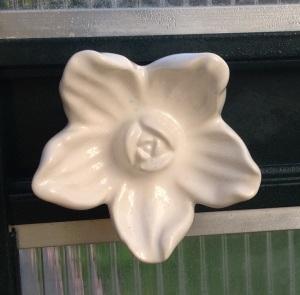 Valkoisen kukan mallinen posliininuppi ovenkahvana kasvihuoneessa