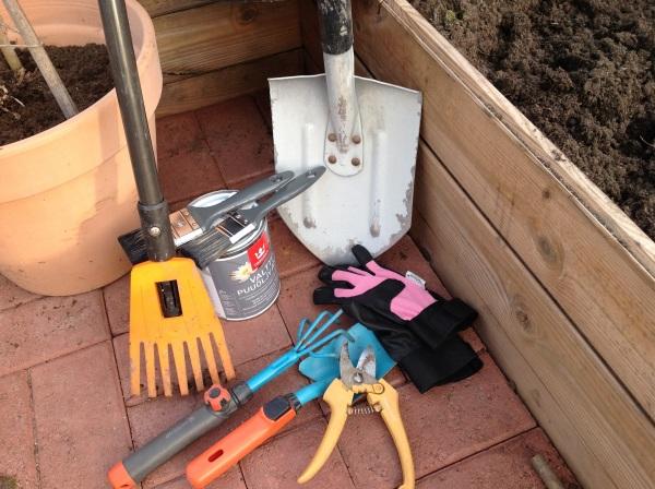Puutarhatyökaluja, lapio, harava, puutarhasakset, hara. Lisäksi puuöljypurkki ja siveltimiä.