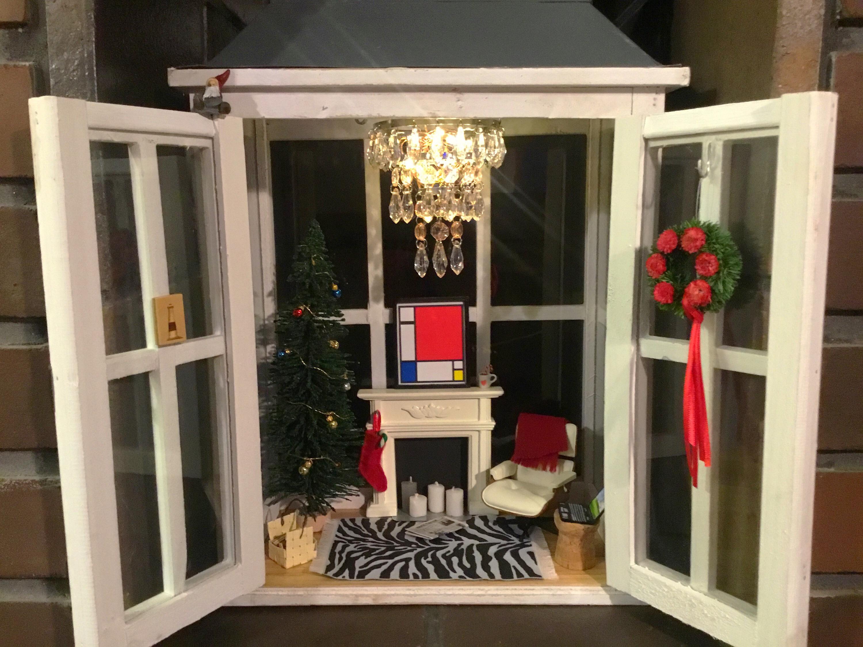 Isoon lyhtyyn tehty jouluinen nukketalo. Joulukuusi, takka ja nojatuoli.