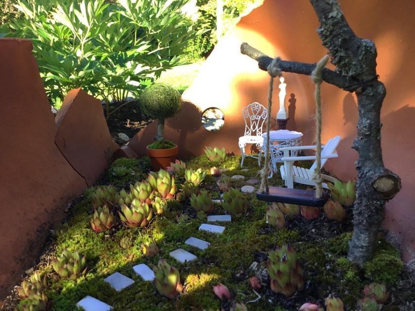 Isoon rikkinäiseen ruukkuun tehty keijupuutarha, jossa on keinu, ja pari tuolia. Alustana kasvaa sammalta ja pieniä mehikasveja.
